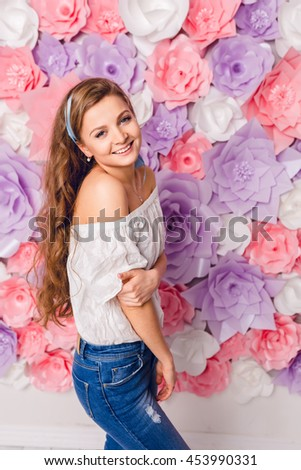 Cute blond girl stands and holds hands down smiling. She has long curly hair and wears blue jeans and white t-shirt off the shoulder. She has pink background covered in flowers. - stock photo