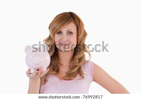 Cute blond-haired woman posing while holding her piggy bank on a white background