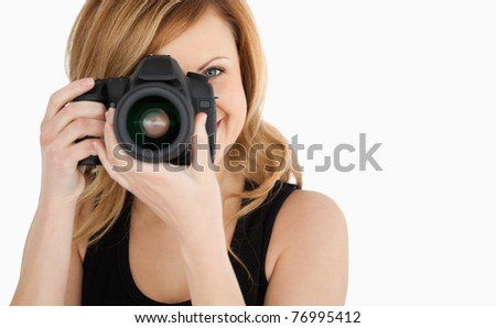 Cute blond-haired woman taking a photo with a camera on a white background - stock photo