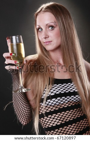 Cute blond in fishnet dress enjoys a champagne flute - stock photo