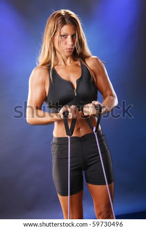 Cute blond in workout gear pulls tension string - stock photo