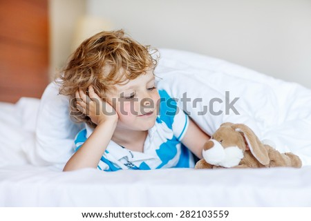 Cute blond kid boy after sleeping in his white bed with toy. Little happy child playing with toy bunny.