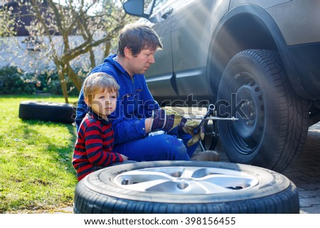 Cute blond kid boy and his father changing wheels on car with pneumatic wrench. Man in uniform teaching his son working with tools. - stock photo