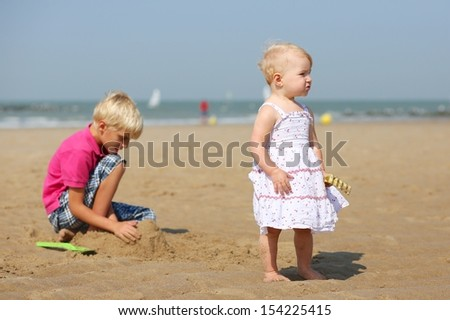 Cute blond little baby girl in beautiful white dress standing on a long sandy beach, her teenager brother is playing with sand behind her, sea shore with yacht boats at the background - stock photo