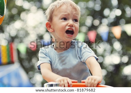 Cute blond little boy crying at a party - stock photo