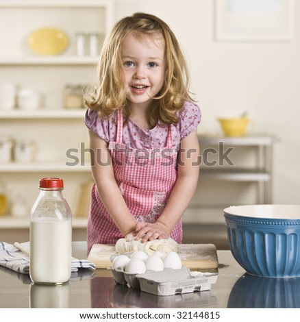 Cute blond little girl making bread in the kitchen. Milk bottle, bowl and eggs on the counter. Square - stock photo