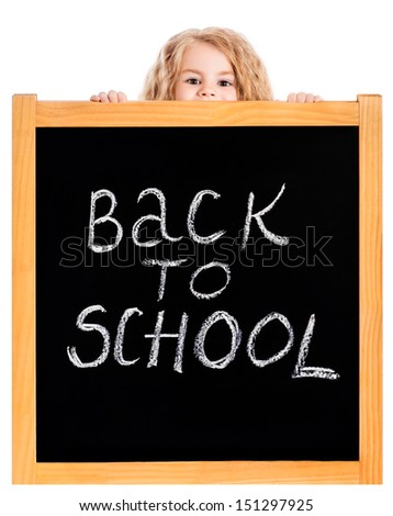 "Cute blond little girl with curly hair peeping out a school black chalkboard with ""back to school"" inscription, isolated on white background - stock photo"