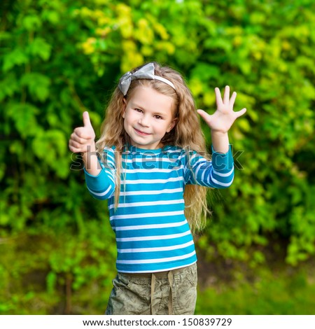 Cute blond little girl with long curly hair showing six fingers (her age) and smiling - stock photo