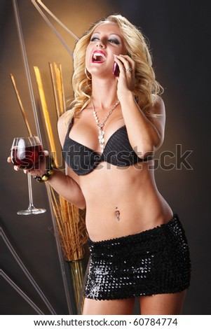 Cute blond on a cellphone call and wine - stock photo