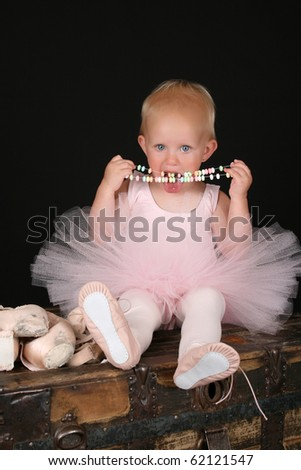 Cute blond toddler wearing a ballet outfit eating candy necklace - stock photo