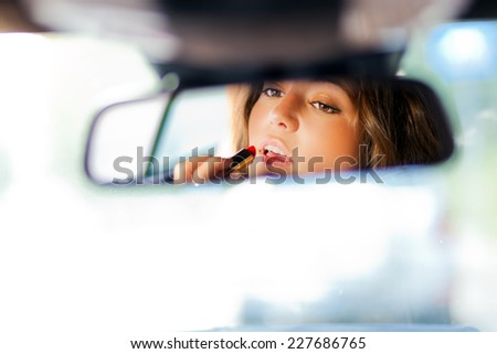 Cute blond woman applying lipstick in a car - stock photo