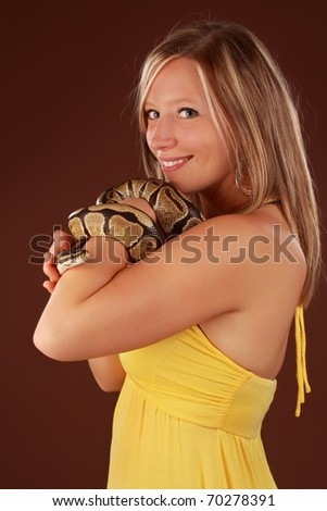 cute blond woman holding a Royal Python snake