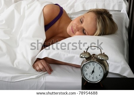 Cute blond woman waking up in bed with alarm clock - stock photo