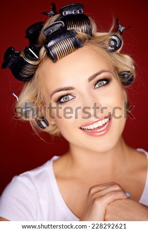 Cute blond woman with her hair in curlers looking at the camera with a beaming playful smile - stock photo