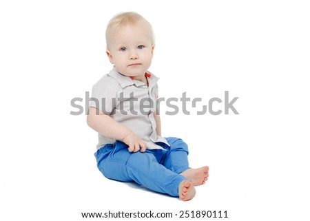 cute blonde blue eyed baby boy sitting over white background and looking into the camera - stock photo