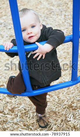 Cute Blonde Boy Climbing on Monkey Bars - stock photo