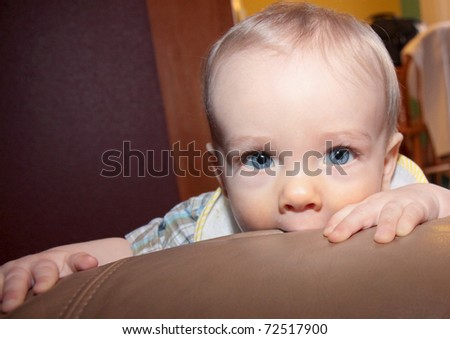 Cute blonde boy with blue eyes chews on furniture while looking into camera - stock photo