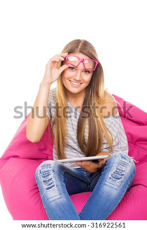 Cute blonde Caucasian teenage girl with tablet and eyeglasses sitting in pink beanbag at home reading or learning. Isolated on white background. - stock photo