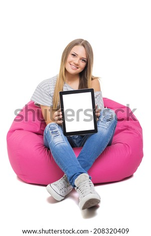 Cute blonde Caucasian teenage student girl showing tablet with white screen looking at camera smiling sitting on beanbag isolated on white background. - stock photo