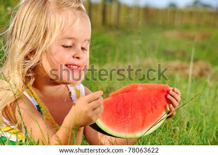 Cute blonde girl eats a watermelon whilst sitting in the grass - stock photo