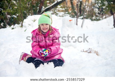 Cute blonde girl in Jerusalem making a snowball while sitting in the snow in her house backyard - stock photo