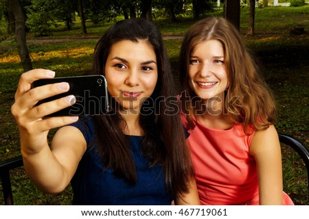 cute blonde girl in peach dress and her dark-haired friend in a dark blue dress walking in a city Park