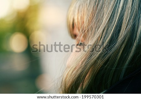 Cute blonde girl in profile against outdoor background - stock photo