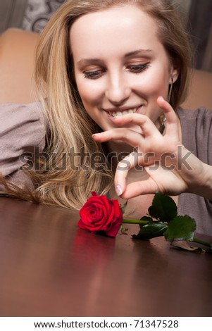 Cute blonde girl with a red rose - stock photo
