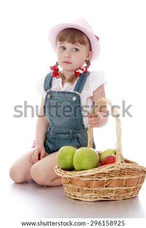 Cute blonde girl with short bangs and braids in which the braided ribbon , summer hat and denim shorts sitting on his knees next to the wicker basket from willow branches which are large apples - - stock photo