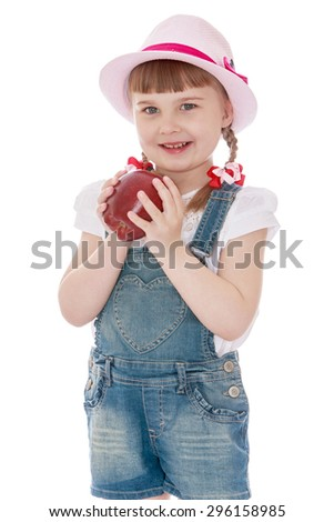Cute blonde girl with short bangs and braids in which the braided ribbon , summer hat and denim shorts holding a big red Apple, close-up - isolated on white background - stock photo
