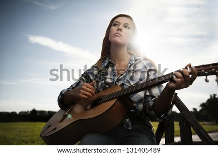 Cute Blonde girl with the guitar sitting on the fence on sunny day - stock photo
