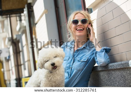 Cute blonde in sunglasses and a bright blue denim shirt emotionally talking on a cell phone. Bichon Frise white dog sitting on the lap of the girl. - stock photo