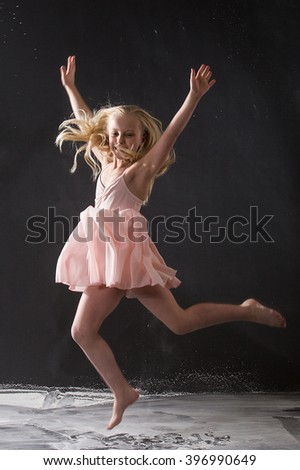 Cute blonde kid jumping in excitement - stock photo