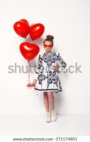 Cute blonde kid little girl posing with red heart shaped balloons and a teddy bear isolated on white. Children fashion photo - stock photo