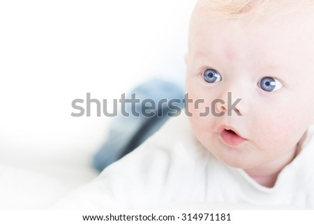 Cute blonde little baby boy with blue eyes. Copy space on left.