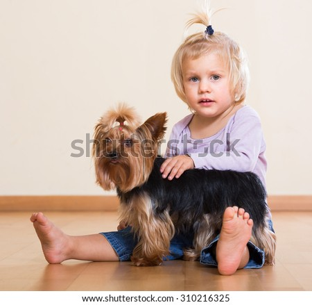 Cute blonde little girl sitting on the floor with Yorkshire Terrier indoor - stock photo