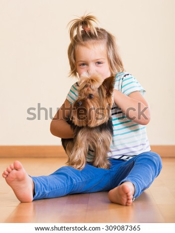 Cute blonde little girl with Yorkshire Terrier indoor - stock photo
