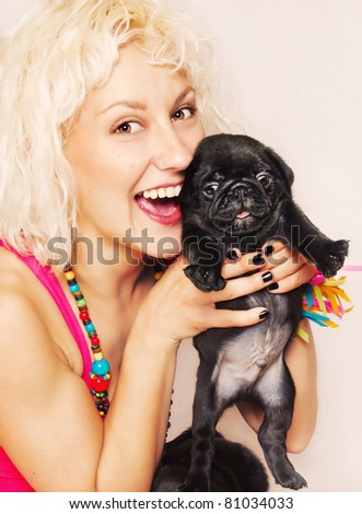 Cute blonde playing with a pug puppy - stock photo