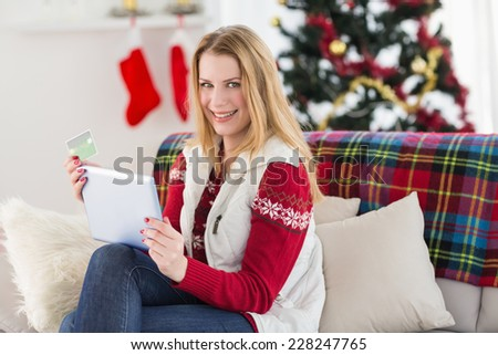 Cute blonde sitting on couch holding credit card and tablet at home in the living room - stock photo