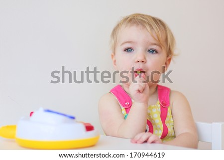 Cute blonde toddler girl eating lollipop sitting indoors - stock photo