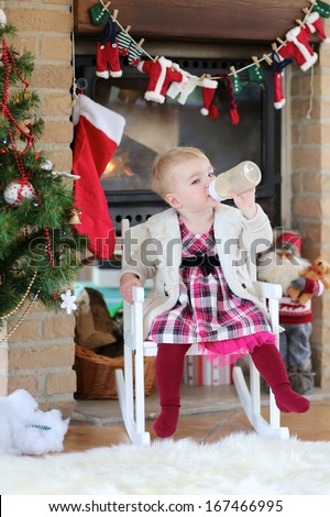 Cute blonde toddler girl in beautiful festive dress sitting in white rocking chair nearby fireplace with santa claus and christmas tree drinking milk from the bottle enjoying a merry christmas day