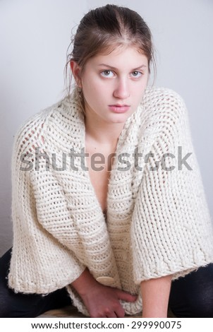 Cute blonde wearing knitted woolen pullover. House wall as background