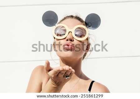 Cute blonde wearing sunglasses and sending a kiss. Outdoors lifestyle - stock photo