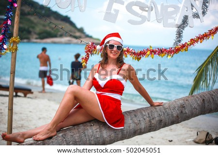 Cute blonde woman in red dress, sunglasses and santa hat sitting on palm tree at exotic tropical beach. Holiday concept for New Years Cards. Koh Samui. Thailand
