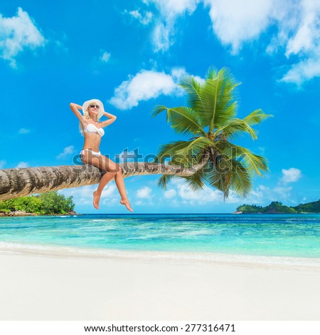 Cute blonde woman in white bikini and hat at palm tree against tropical island beach and azure ocean - vacation background