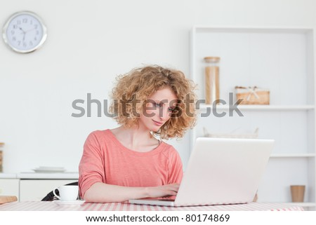 Cute blonde woman relaxing with her laptop while sitting in the kitchen in her apartment - stock photo