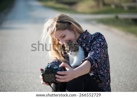 Cute blonde woman taking self portrait with a cat - stock photo