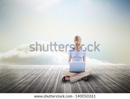 Cute blonde woman using laptop over wooden boards leading out to the horizon - stock photo