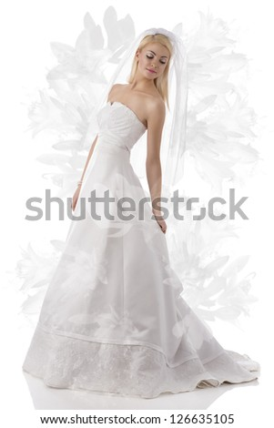 cute blonde woman with long wedding dress, white veil and pearl bracelet. Some flowers on background - stock photo