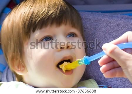 Cute blue eye baby eat - stock photo